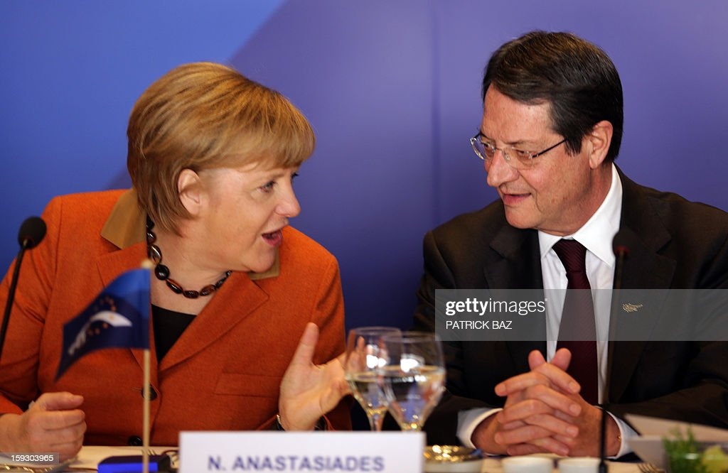 German Chancellor Angela Merkel (L) speaks with Nicos Anastasiades, President of the Democratic Rally of Cyprus (DISY), at the start of the extraordinary European People's Party (EPP) summit in Limassol on January 11, 2013, attended by EU heads of state, party leaders, and the presidency of the EPP.
