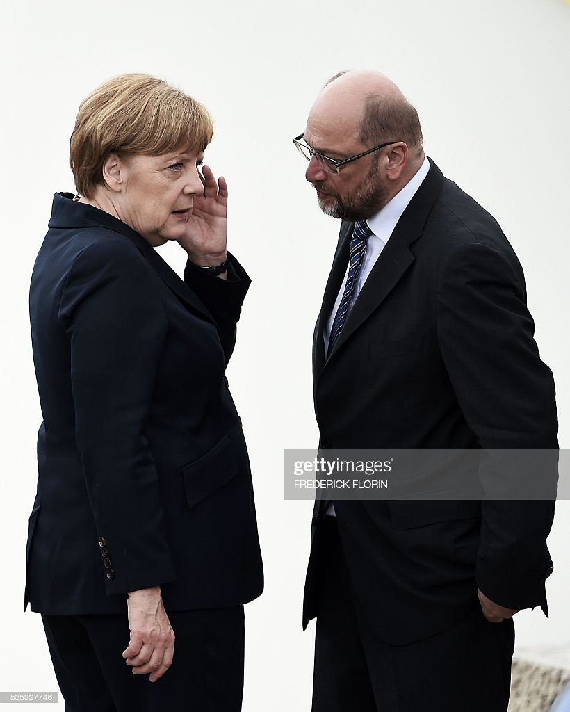 German Chancellor Angela Merkel (L) speaks with President of European Parliament Martin Schulz during a remembrance ceremony to mark the centenary of the battle of Verdun, at the Douaumont Ossuary (Ossuaire de Douaumont), northeastern France, on May 29, 2016. The battle of Verdun, in 1916, was one of the bloodiest episodes of World War I. The offensive which lasted 300 days claimed more than 300,000 lives. / AFP / FREDERICK