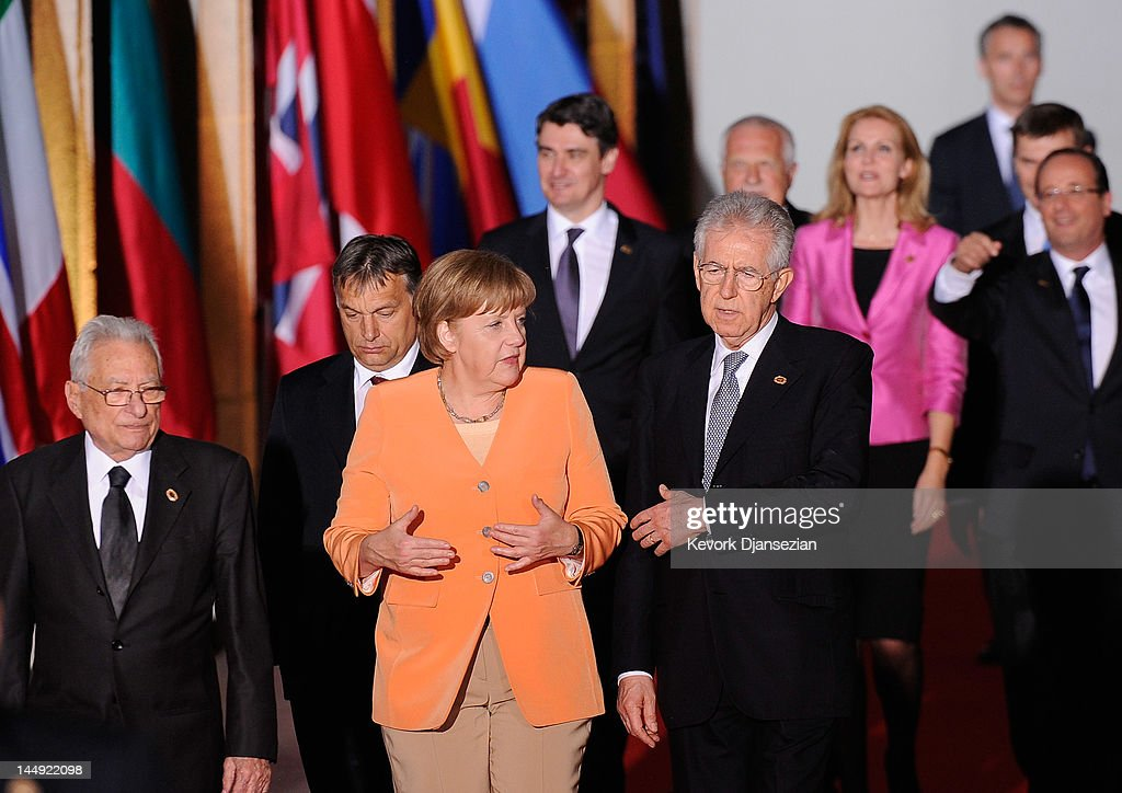 German Chancellor Angela Merkel (L) speaks with Prime Minister of Italy Mario Monti as they walk under the Soldier Field colonnades to the family photo during NATO Summit on May 20, 2012 in Chicago, Illinois. As sixty heads of state converge for the two day summit that will address the situation in Afghanistan, among other global defense issues, thousands of demonstrators have taken to the streets to protest.
