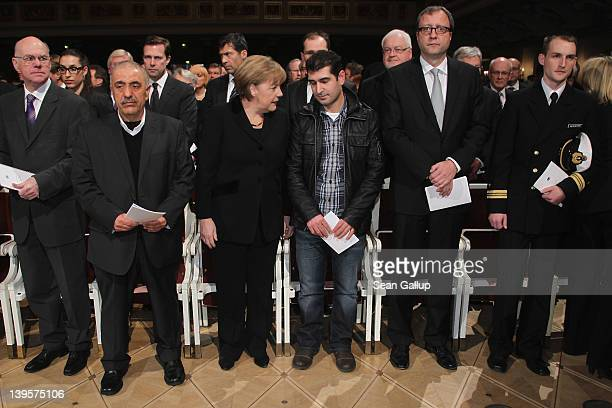 German Chancellor Angela Merkel speaks with relatives of victims at a state commemoration for the victims of the NSU neoNazi murders at the...