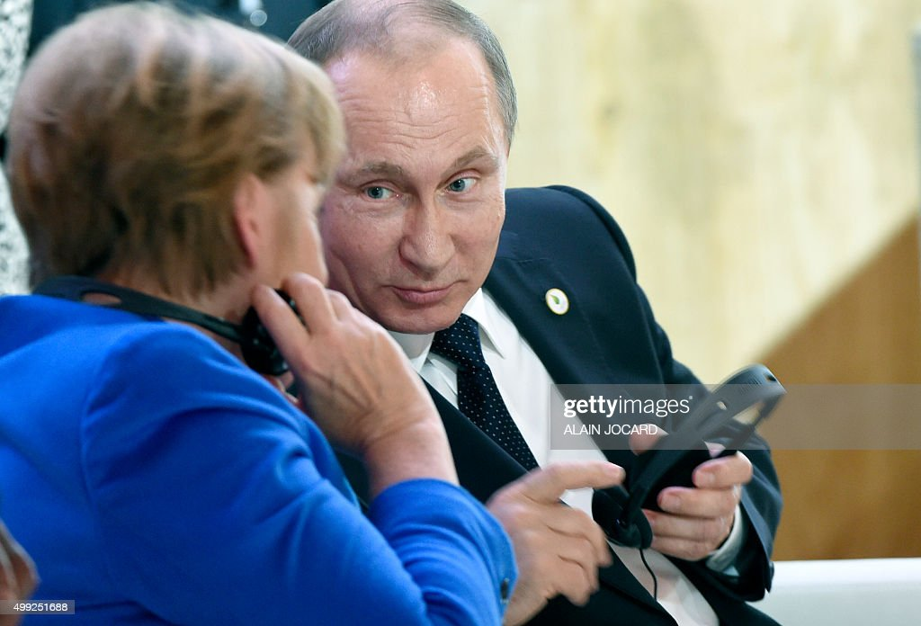 German Chancellor Angela Merkel speaks with Russian President Vladimir Putin during the opening day of the World Climate Change Conference 2015 on...