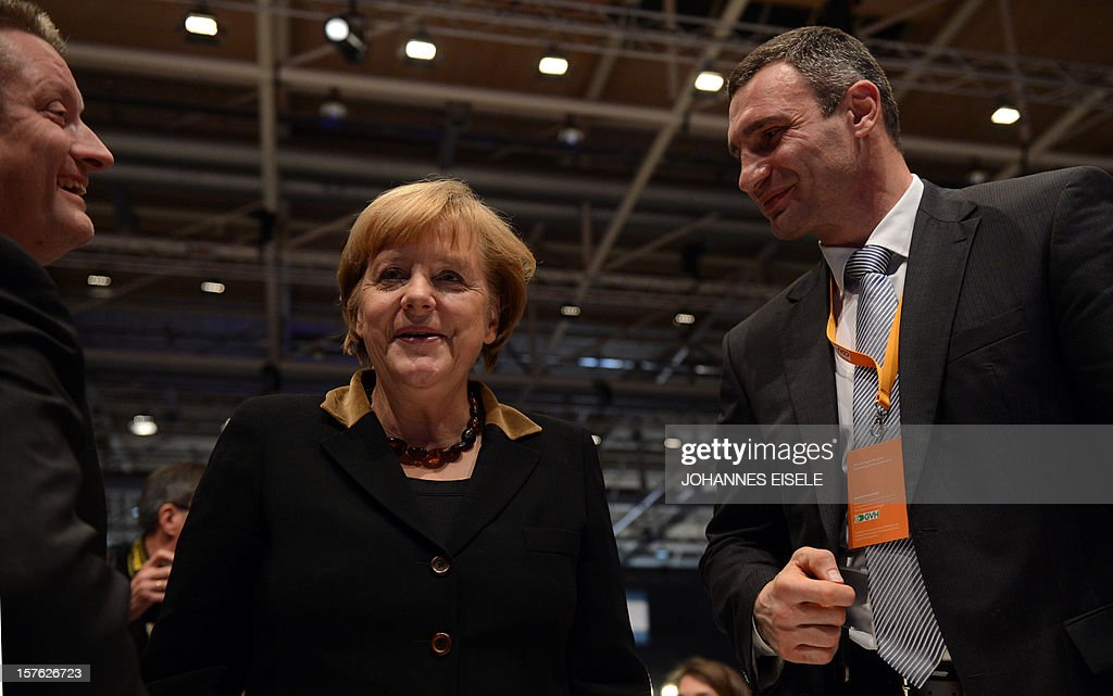German Chancellor Angela Merkel speaks with Ukrainian box champion and member of Ukrainian Parliament Vitali Klitschko (R) and CDU Secretary General Hermann Groehe (L) during a congress of Germany's ruling conservative Christian Democratic Union (CDU) party on December 4, 2012 in Hanover, central Germany. German Chancellor Angela Merkel was re-elected head of her conservative Christian Democrats (CDU) by more than 97 percent of delegates' votes at a two-day party congress. It was Merkel's best result since she took over as chairman of the CDU in 2000 and comes as she gears up for fighting for a third term at the helm of Europe's top economy in elections expected in September 2013. AFP PHOTO / JOHANNES EISELE