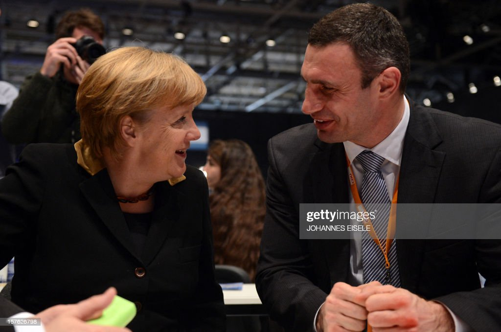 German Chancellor Angela Merkel speaks with Ukrainian Ukrainian box champion and member of Ukrainian Parliament Vitali Klitschko during a congress of Germany's ruling conservative Christian Democratic Union (CDU) party on December 4, 2012 in Hanover, central Germany. German Chancellor Angela Merkel was re-elected head of her conservative Christian Democrats (CDU) by more than 97 percent of delegates' votes at a two-day party congress. It was Merkel's best result since she took over as chairman of the CDU in 2000 and comes as she gears up for fighting for a third term at the helm of Europe's top economy in elections expected in September 2013. AFP PHOTO / JOHANNES EISELE