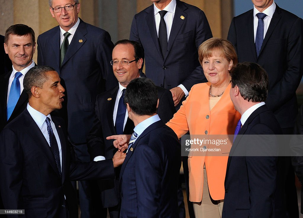 German Chancellor Angela Merkel (C) speaks with U.S. President Barack Obama (L) during family photo under the Soldier Field colonnades during the NATO Summit on May 20, 2012 in Chicago, Illinois. As sixty heads of state converge for the two day summit that will address the situation in Afghanistan, among other global defense issues, thousands of demonstrators have taken to the streets to protest.