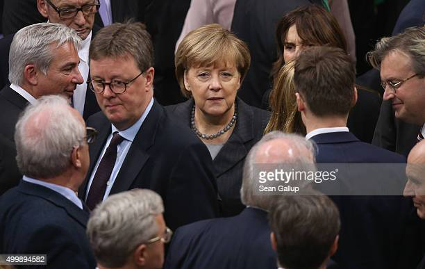 German Chancellor Angela Merkel stands among colleagues after casting her ballot in a vote at the Bundestag on Germany's participation in a...