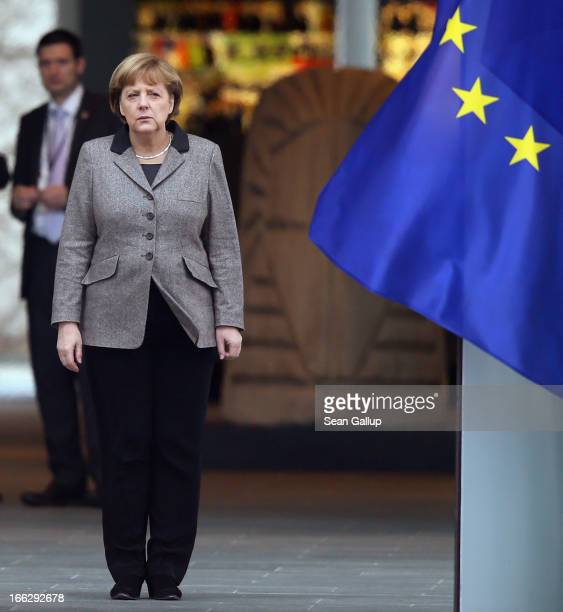 German Chancellor Angela Merkel stands at the entrance to the Chancellery next to a flag of the European Union shortly before the arrival of Indian...