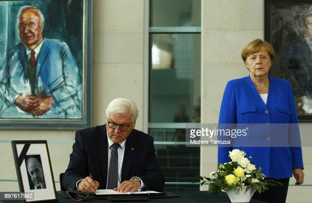 German chancellor Angela Merkel stands by German Federal President FrankWalter Steinmeier as he signs a book of condolences next to a portrait of...