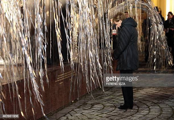 German Chancellor Angela Merkel stands in front of the Holocaust Memorial of the Hungarian Jewish Martyrs by Hungarian sculptor Imre Varga behind...