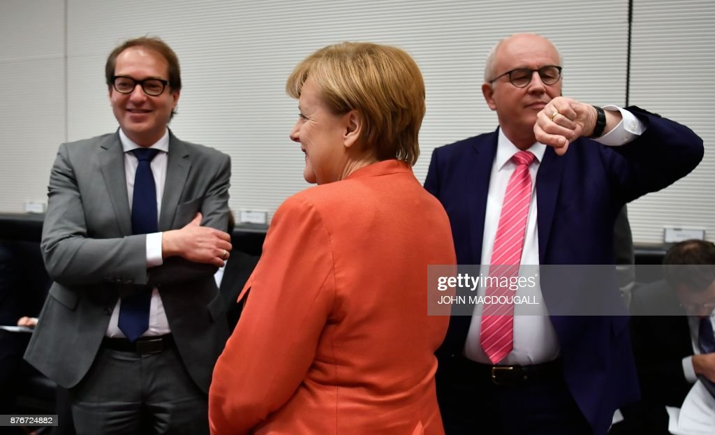 German Chancellor Angela Merkel stands inbetween German Transport Minister Alexander Dobrindt (L) and Parliamentary group leader of the conservative CDU/CSU faction, Volker Kauder (R) prior to a parliamentary group meeting of the conservative CDU/CSU faction on November 20, 2017 in Berlin. Following more than a month of gruelling negotiations, the leader of the pro-business FDP, Christian Lindner, walked out of talks overnight, on November 19, 2017 saying there was no 'basis of trust' to forge a government with Merkel's conservative alliance CDU-CSU and the ecologist Greens. / AFP PHOTO / John MACDOUGALL