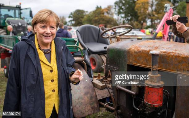 German Chancellor Angela Merkel stands next to a vintage tractor at a harvest festival as she tours the city of Lauterbach on the Baltic Island of...
