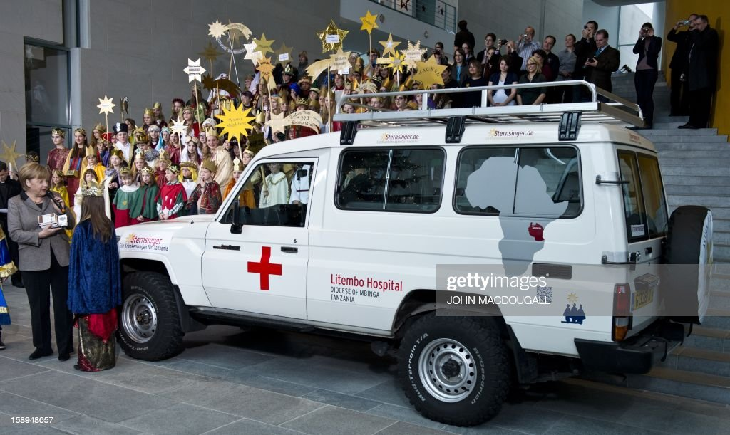 German Chancellor Angela Merkel (L) stands next to an ambulance as she hosted young Carol singers at the Chancellery in Berlin on January 4 , 2013. Carol singers visited the Chancellery as part of the 'Three King's Action' charity which focused on healthcare in Tanzania this year. The Carol singers will use the donations received to send an ambulance to Tanzania.