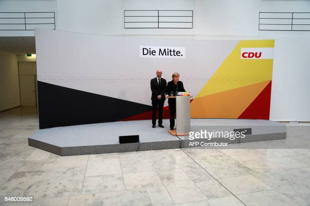 German Chancellor Angela Merkel stands next to CDU secretary general Peter Tauber as she gives a statement on September 12 2017 in Berlin to express...
