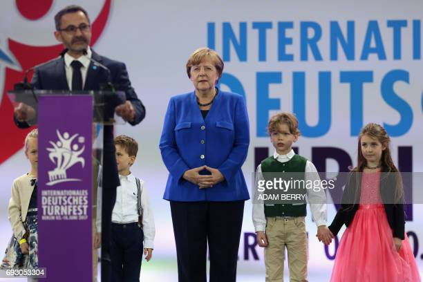 German Chancellor Angela Merkel stands with children as Alfons Hoelzl president of the German Gymnastics Associaion speaks during the Stadium Gala of...