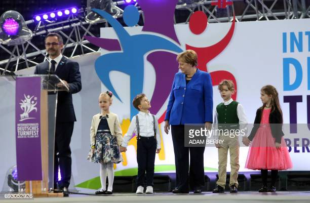 German Chancellor Angela Merkel stands with children during the Stadium Gala of the 2017 Deutsches Turnfest at the Olympic Stadium in Berlin on June...