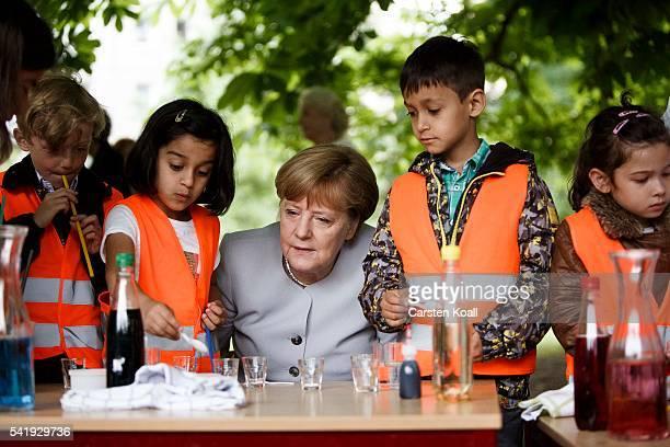 German Chancellor Angela Merkel stands with children on a laboratory bench during her visit to the Weydemeyerstrasse Kindergarten on Jne 21 2016 in...
