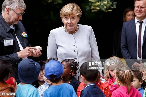 German Chancellor Angela Merkel stands with children on a laboratory station during her visit to the Weydemeyerstrasse Kindergarten on Jne 21 2016 in...