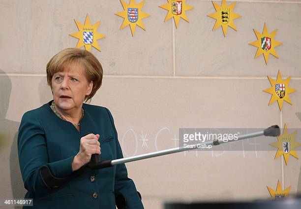 German Chancellor Angela Merkel stands with crutches at a podium after speaking at a gathering of child Epiphany singers dressed as the Three Kings...