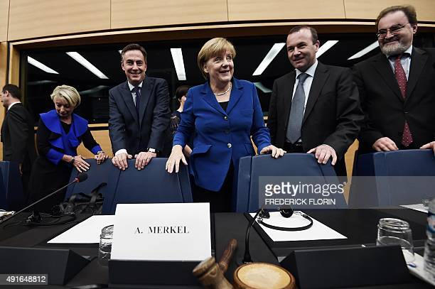 German Chancellor Angela Merkel stands with delegates as she prepares to take her seat upon arrival at the European Parliament in Strasbourg eastern...