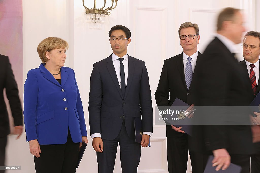 German Chancellor Angela Merkel stands with Vice Chancellor and Economy Minister Philipp Roesler (C) and Foreign Minister <a gi-track='captionPersonalityLinkClicked' href=/galleries/search?phrase=Guido+Westerwelle&family=editorial&specificpeople=208748 ng-click='$event.stopPropagation()'>Guido Westerwelle</a> (3rd from R), who are both members of the German Free Democrats (FDP), after they and other members of the German government received their dismissal certificates from German President Joachim Gauck at a ceremony for the outgoing German government at Bellevue Palace on October 22, 2013 in Berlin, Germany. The ministers will stay on in their functions until a new government is formed, which will most likely be a coalition between the German Christian Democrats (CDU) and the German Social Democrats (SPD). For the FDP members the ceremony today is especially poignant, as the party failed in recent German elections to receive the 5% minimum of votes necessary to retain its seats in the Bundestag, which means the party no longer has political say on the federal level.