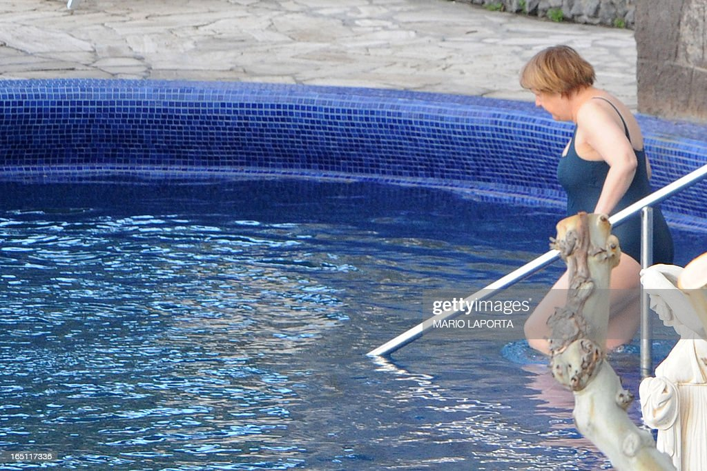 German Chancellor Angela Merkel takes a bath in the swimming pool of the Aphrodite Terme in the coastal town of Sant'Angelo d'Ischia on the southern Italy's Island of Ischia during their Easter holiday on March 31, 2013.