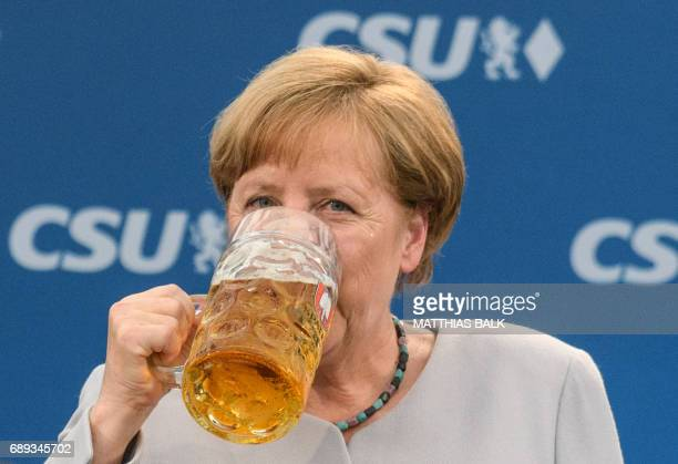 German Chancellor Angela Merkel takes a sip of beer after delivering a speech during a joint campaigning event of the Christian Democratic Union and...
