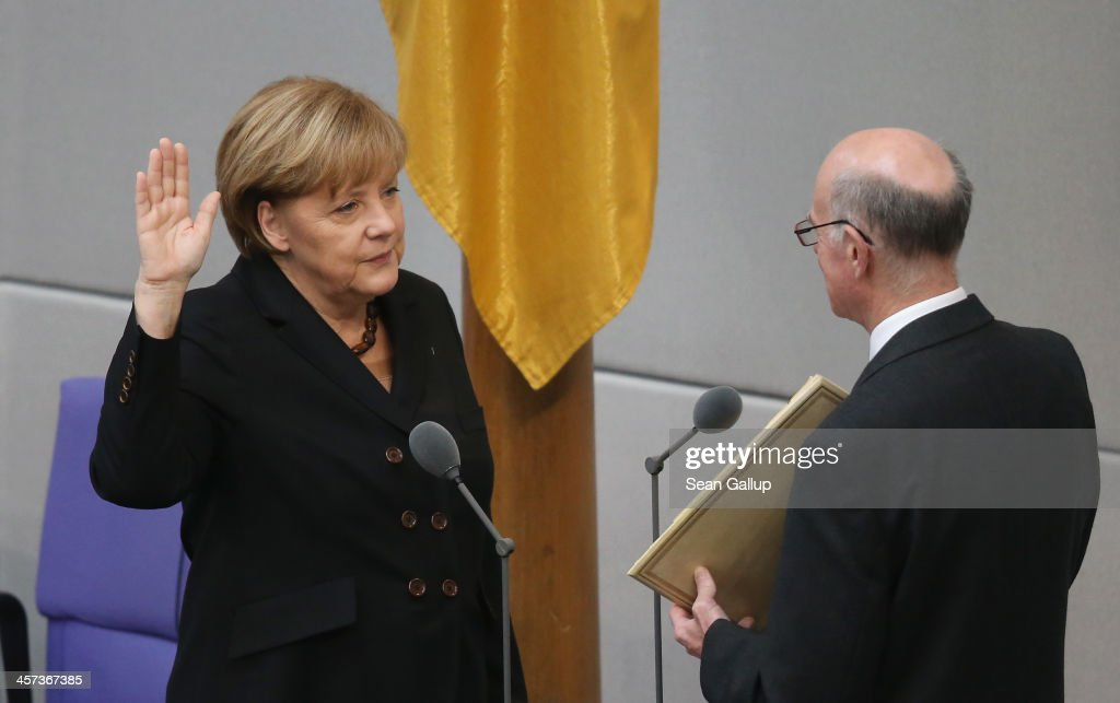 German Chancellor <a gi-track='captionPersonalityLinkClicked' href=/galleries/search?phrase=Angela+Merkel&family=editorial&specificpeople=202161 ng-click='$event.stopPropagation()'>Angela Merkel</a> takes her oath of office for her third term as chancellor from Bundestag President <a gi-track='captionPersonalityLinkClicked' href=/galleries/search?phrase=Norbert+Lammert&family=editorial&specificpeople=575522 ng-click='$event.stopPropagation()'>Norbert Lammert</a> at the Bundestag during ceremonies in which the new German government was sworn in on December 17, 2013 in Berlin, Germany. The new government is a coalition between the German Christian Democrats (CDU), the Bavarian Christian Democrats (CSU) and German Social Democrats (SPD) following federal elections held in September.