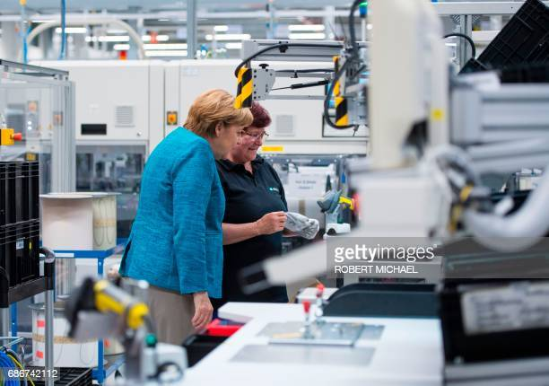German Chancellor Angela Merkel talks to a employee during a visit to the new plant of the ACCUMOTIVE company producing accumulators for cars in...