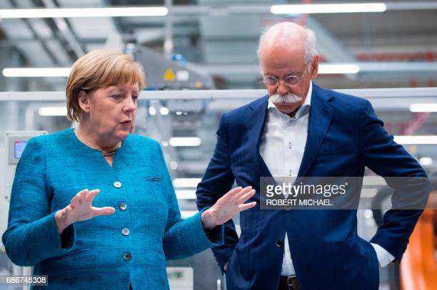 German Chancellor Angela Merkel talks to CEO of German carmaker Daimler and MercedesBenz Dieter Zetsche during a visit to the new plant of the...