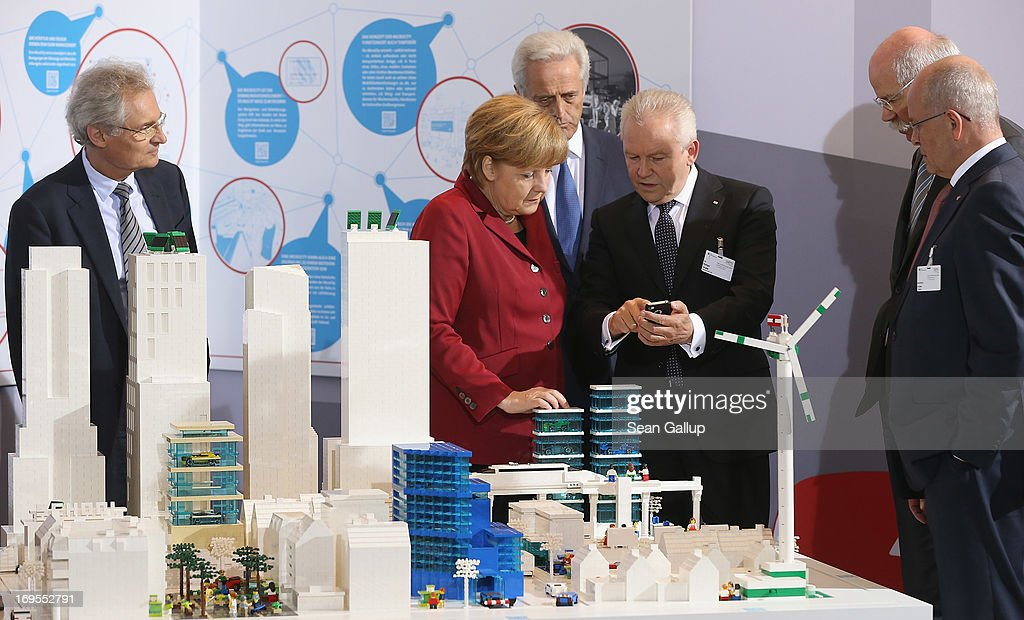 German Chancellor Angela Merkel talks to Deutsche Bahn head Ruediger Grube as Transport Minister <a gi-track='captionPersonalityLinkClicked' href=/galleries/search?phrase=Peter+Ramsauer&family=editorial&specificpeople=770626 ng-click='$event.stopPropagation()'>Peter Ramsauer</a> stands behind and <a gi-track='captionPersonalityLinkClicked' href=/galleries/search?phrase=Henning+Kagermann&family=editorial&specificpeople=961608 ng-click='$event.stopPropagation()'>Henning Kagermann</a> (L), president of Acatech, looks on while visiting the MicroCity stand at the Electro-Mobility Conference at the Berlin Congress Center on May 27, 2013 in Berlin, Germany. The government-sponsored conference brought together heads of auto companies and auto parts suppliers. Chancellor Merkel has announced the goal of having one million electric cars on Germany's streets by 2020.