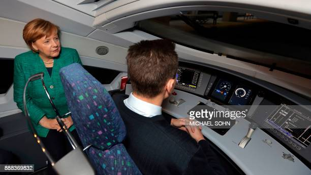 German Chancellor Angela Merkel talks to driver Martin Spiegelhauer as she attends a part of the opening passage of a special ICE railway route...