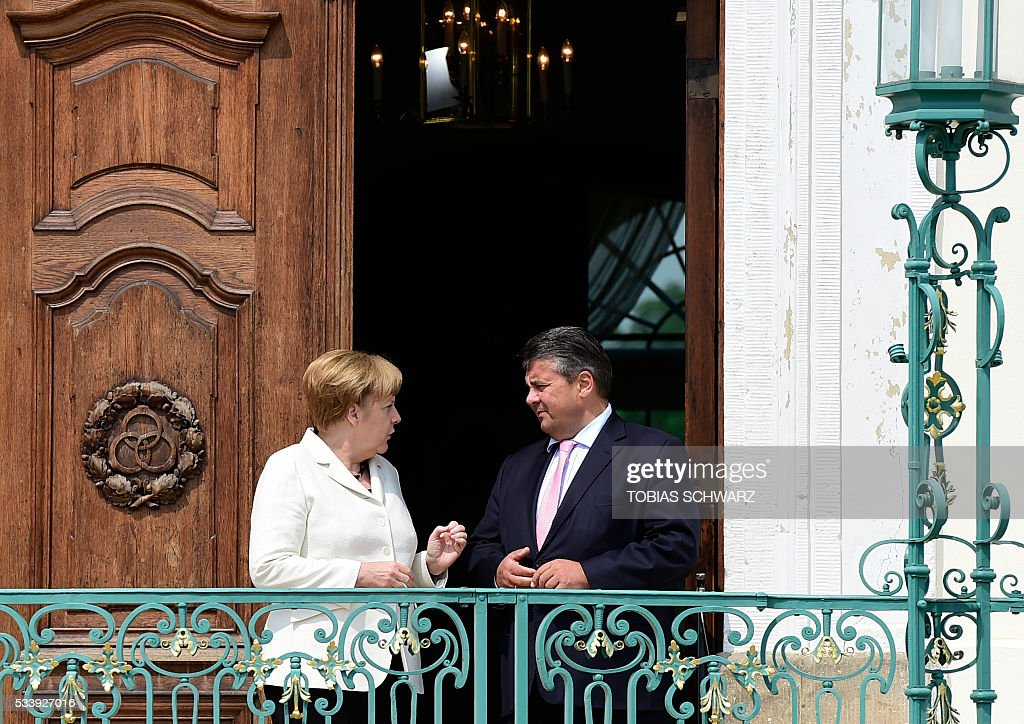German Chancellor Angela Merkel talks to German Vice Chancellor, Economy and Energy Minister Sigmar Gabriel during a closed meeting of the German cabinet at Meseberg Palace on May 24, 2016 in Meseberg, northeastern Germany. / AFP / TOBIAS