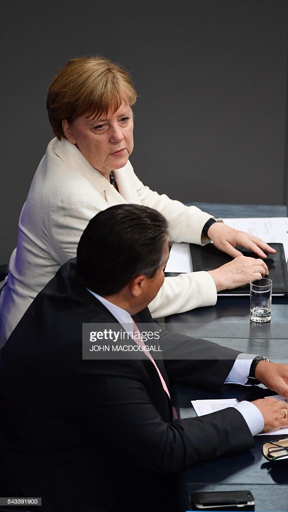 German Chancellor Angela Merkel (L) talks to German Vice Chancellor, Economy and Energy Minister Sigmar Gabriel after she outlined to parliament her vision for the future of Europe following Britain's decision to leave the EU at a special plenary session at the German lower house of Parliament Bundestag in Berlin, on June 28, 2016. / AFP / John MACDOUGALL