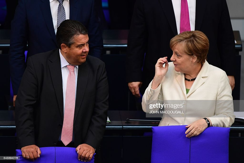 German Chancellor Angela Merkel (R) talks to German Vice Chancellor, Economy and Energy Minister Sigmar Gabriel after a special plenary session on Brexit at the German lower house of Parliament Bundestag in Berlin, on June 28, 2016. / AFP / John MACDOUGALL