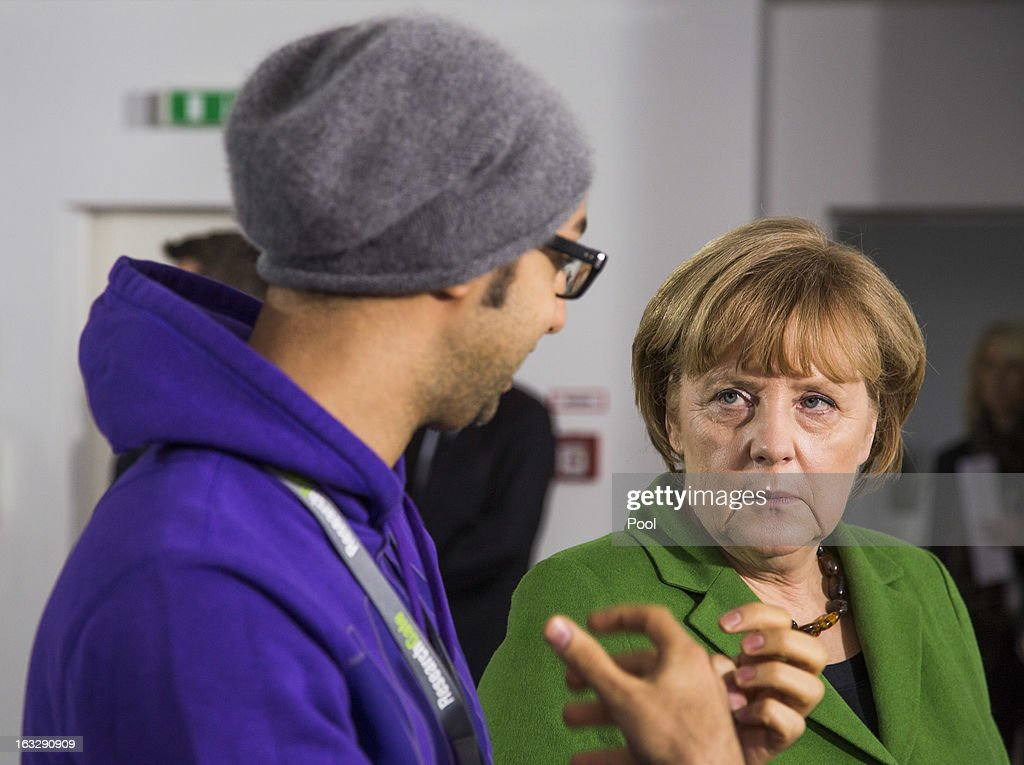 German Chancellor Angela Merkel talks to manager Ijad Madisch during her visit of the company Research Gate on March 7, 2013 in Berlin, Germany. Chancellor Merkel and Economy Minister Philipp Roesler visited young internet companies and talked to financiers.