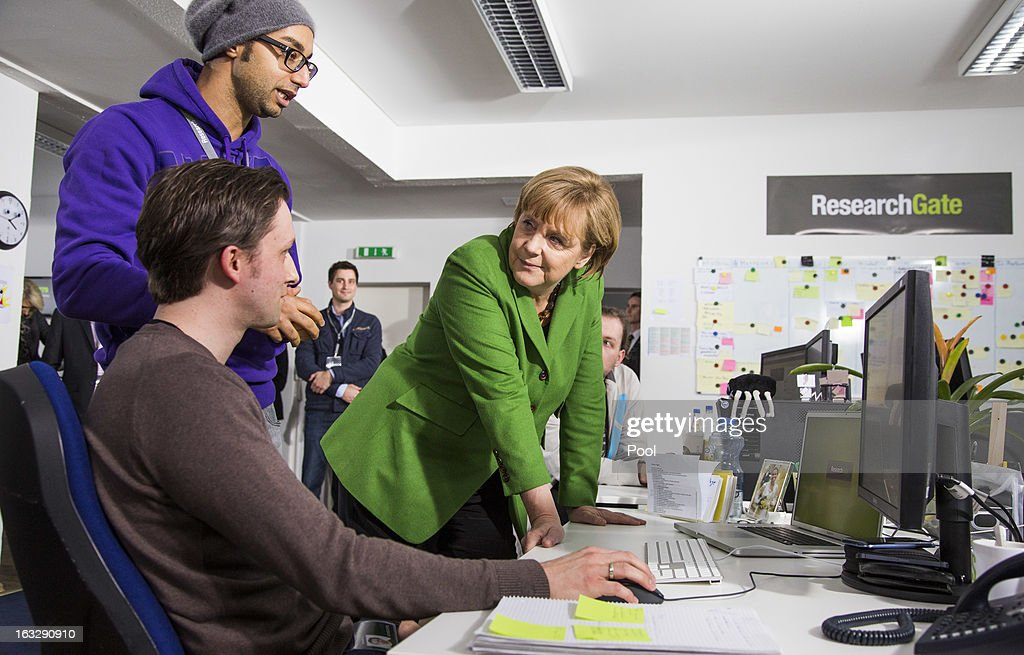 German Chancellor <a gi-track='captionPersonalityLinkClicked' href=/galleries/search?phrase=Angela+Merkel&family=editorial&specificpeople=202161 ng-click='$event.stopPropagation()'>Angela Merkel</a> talks to manager Ijad Madisch (up) during her visit of the company Research Gate on March 7, 2013 in Berlin, Germany. Chancellor Merkel and Economy Minister Philipp Roesler visited young internet companies and talked to financiers.