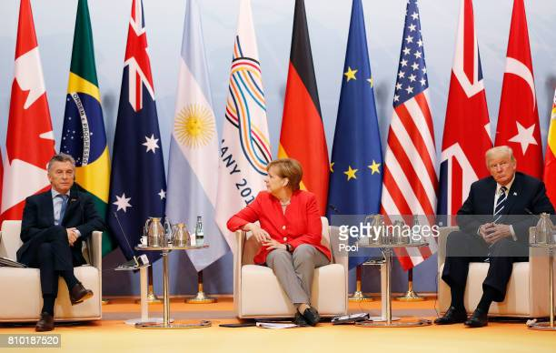 German Chancellor Angela Merkel talks to Mauricio Macri of Argentina and US President Donald Trump during the G20 leaders retreat as part of the G20...