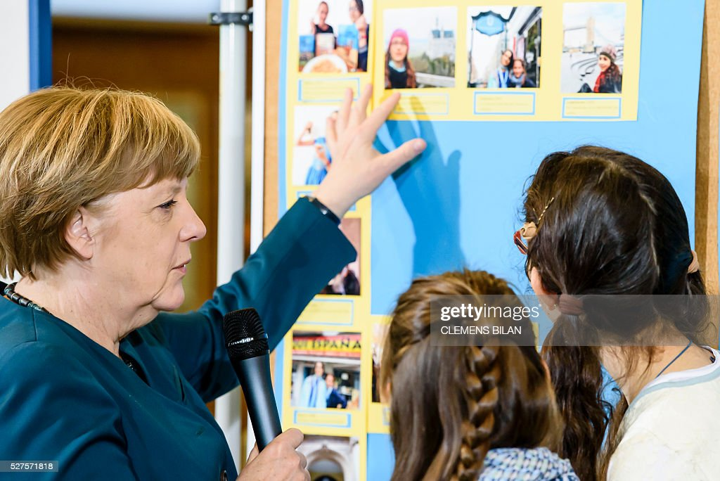 German Chancellor Angela Merkel talks to pupils during her visit of the Lycee Francais School in Berlin on May 03, 2016. / AFP / CLEMENS