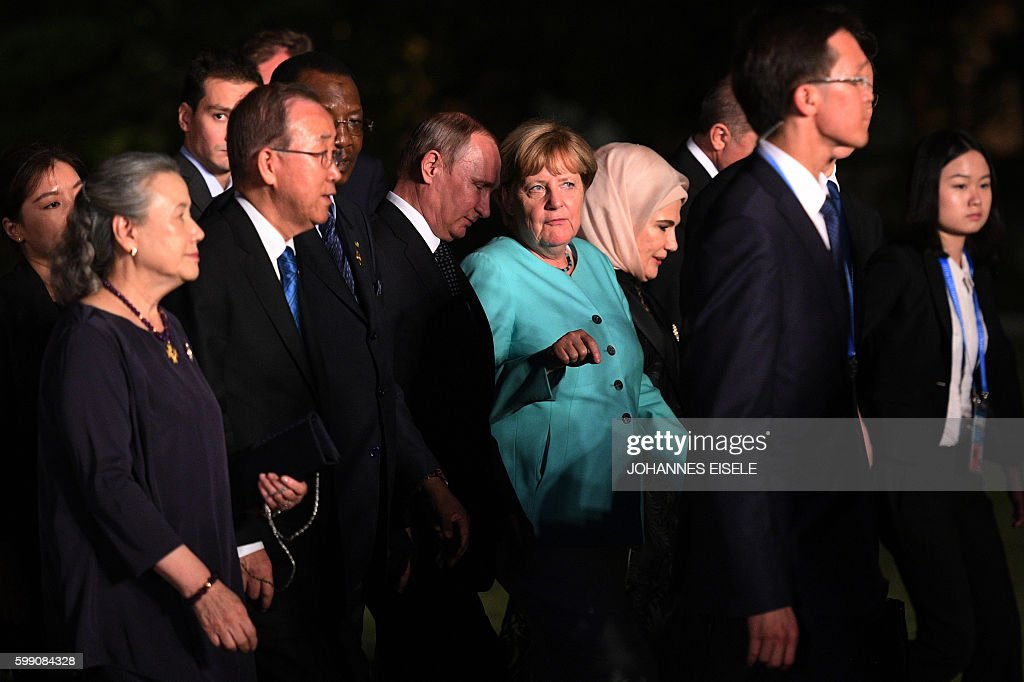 TOPSHOT - German Chancellor Angela Merkel (centre R) talks to Russia's President Vladimir Putin (centre L) as G20 leaders and their spouses walk for a group picture prior to a dinner banquet at the G20 Summit in Hangzhou on September 4, 2016. World leaders are gathering in Hangzhou for the 11th G20 Leaders Summit from September 4 to 5. / AFP / JOHANNES