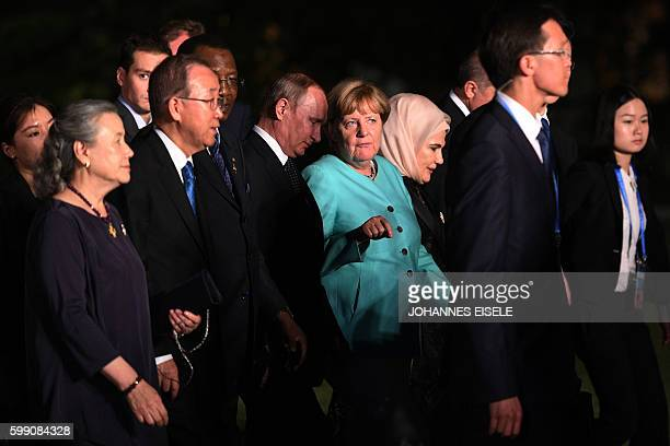 TOPSHOT German Chancellor Angela Merkel talks to Russia's President Vladimir Putin as G20 leaders and their spouses walk for a group picture prior to...