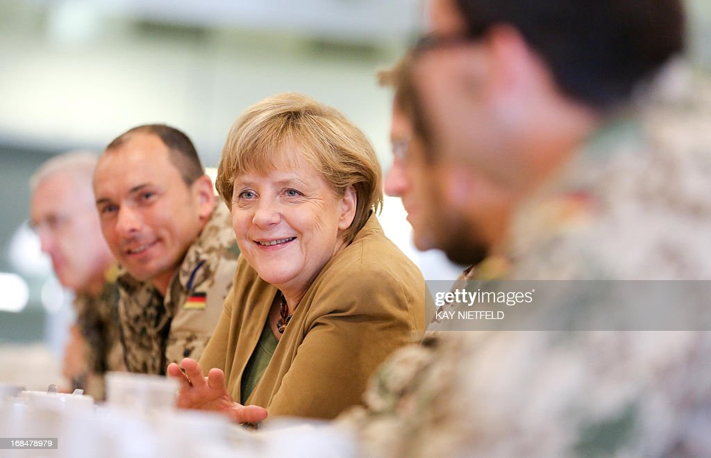 German Chancellor Angela Merkel (C) talks to soldiers during a visit to the base of German army Bundeswehr in Kunduz, Afghanistan, on May 10, 2013.Their surprise visit comes six days after a German soldier was killed and another wounded in an attack by insurgents in northern Afghanistan.