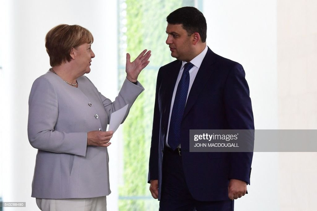 German chancellor Angela Merkel (L) talks to Ukraine's Prime Minister Volodymyr Groysman ahead a joint press conference at the chancellery in Berlin on June 27, 2016. / AFP / John MACDOUGALL