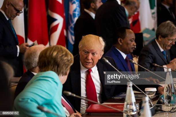 German Chancellor Angela Merkel talks to US President Donald Trump during the G7 Summit expanded session in Taormina Sicily on May 27 2017
