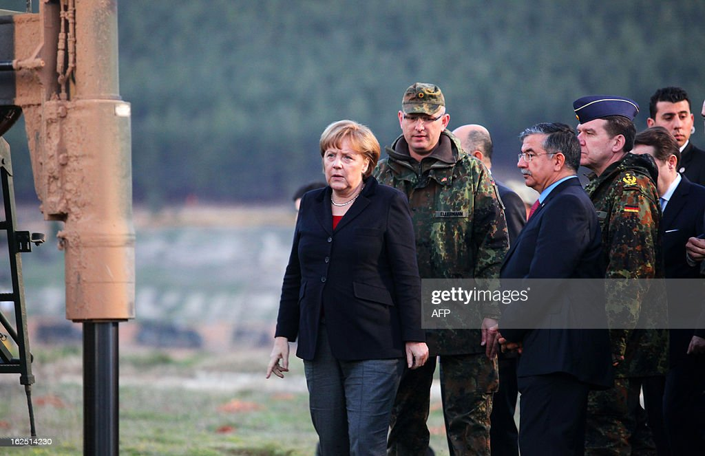 German Chancellor Angela Merkel (L) talks with a German soldier as she visits the site where Patriot missile batteries were installed near the city of Kahramanmaras, on February 24, 2013. Germany's defence minister inspected Patriot missile batteries close to the Syria-Turkey border on Saturday and said they delivered a 'clear warning' to Damascus that NATO would not tolerate missiles being fired into Turkey. AFP PHOTO/STR