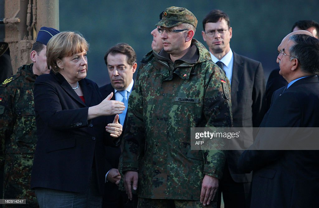 German Chancellor Angela Merkel (L) talks with a German soldier as she visits the site where Patriot missile batteries are installed near the city of Kahramanmaras, on February 24, 2013. Germany's defence minister inspected Patriot missile batteries close to the Syria-Turkey border on Saturday and said they delivered a 'clear warning' to Damascus that NATO would not tolerate missiles being fired into Turkey.