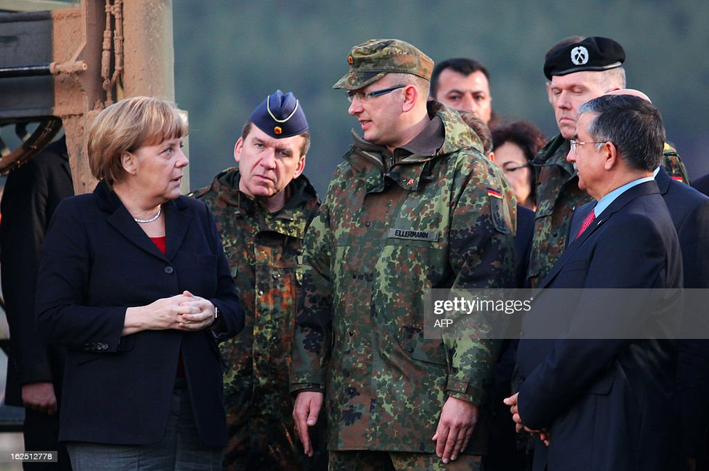 German Chancellor Angela Merkel (L) talks with a German soldier next to Turkish Defence Minister Ismet Yilmaz (R) during a visit on the site where Patriot missile batteries are installed near the city of Kahramanmaras, on February 24, 2013. Germany's defence minister inspected Patriot missile batteries close to the Syria-Turkey border on Saturday and said they delivered a 'clear warning' to Damascus that NATO would not tolerate missiles being fired into Turkey. AFP PHOTO/STR