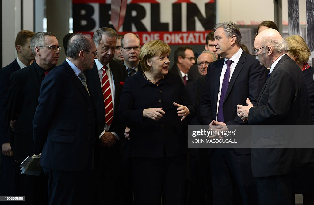 German Chancellor Angela Merkel (C) talks with Andreas Nachama (R), director of the open-air documentation center Topographie des Terrors, Berlin's mayor Klaus Wowereit (2nd R) and Minister of State at the German Chancellery and Representative of the Federal Government for Culture Bernd Neumann (4th L) after the opening of the exhibition 'Berlin 1933 On the Path to Dictatorship', tracing Adolf Hitler's rise to power in Germany in 1933 to mark 80 years since he became chancellor, on January 30, 2013 at the open-air documentation center Topographie des Terrors in Berlin. The exhibition located at the former headquarters of the Gestapo, the secret police of the Nazi regime, traces Hitler's first months in power through photos, newspapers and posters. AFP PHOTO / JOHN MACDOUGALL