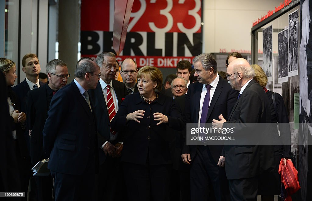 German Chancellor Angela Merkel (C) talks with Andreas Nachama (R), director of the open-air documentation center Topographie des Terrors, Berlin's mayor Klaus Wowereit (2nd R) and Minister of State at the German Chancellery and Representative of the Federal Government for Culture Bernd Neumann (5th L) after the opening of the exhibition 'Berlin 1933 On the Path to Dictatorship', tracing Adolf Hitler's rise to power in Germany in 1933 to mark 80 years since he became chancellor, on January 30, 2013 at the open-air documentation center Topographie des Terrors in Berlin. The exhibition located at the former headquarters of the Gestapo, the secret police of the Nazi regime, traces Hitler's first months in power through photos, newspapers and posters. AFP PHOTO / JOHN MACDOUGALL