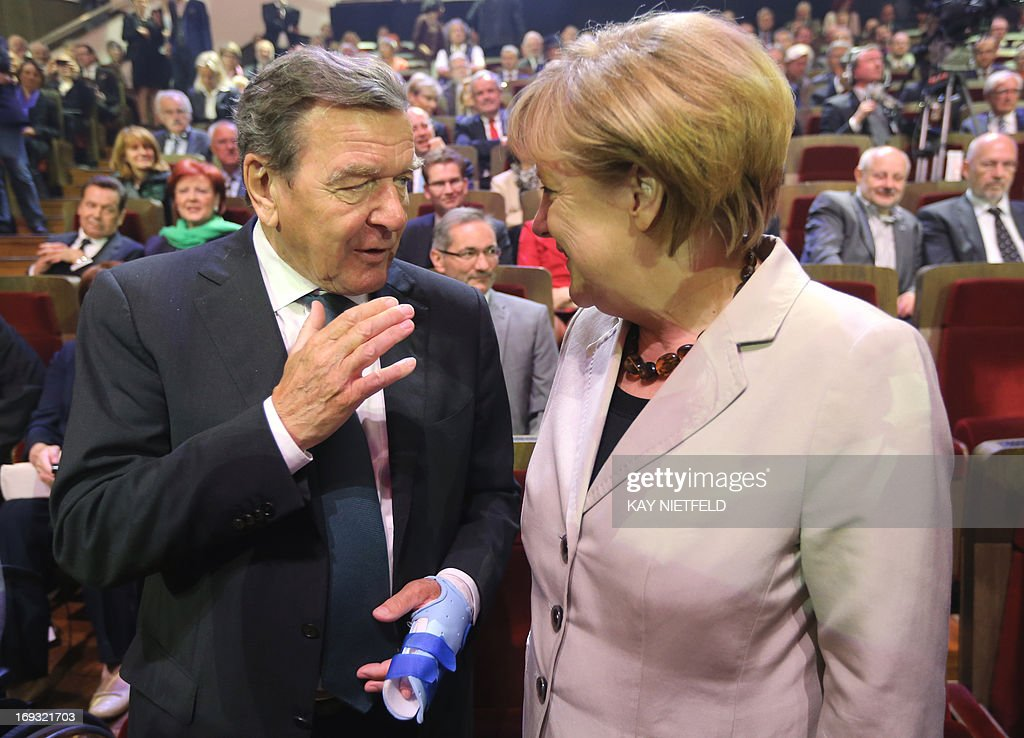 German Chancellor Angela Merkel talks with former German Chancellor Gerhard Schroeder (L) at the Gewandhaus concert hall in Leipzig, eastern Germany, as they arrive to attend festivities to mark the German social democratic SPD party's 150th anniversary on May 23, 2013. The SPD, Europe's oldest political party, has invited nearly 50 current and former heads of state and government as it celebrates 150th birthday and its turbulent history, which saw it advance workers rights and suffer persecution by the Nazis. The SPD was founded on May 23, 1863 in Leipzig as the 'Allgemeiner Deutscher Arbeiterverein' (common German worker's club).