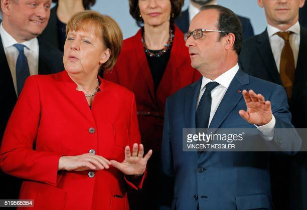 TOPSHOT German Chancellor Angela Merkel talks with French President Francois Hollande as they pose for a family photo for the 18th FrancoGerman...