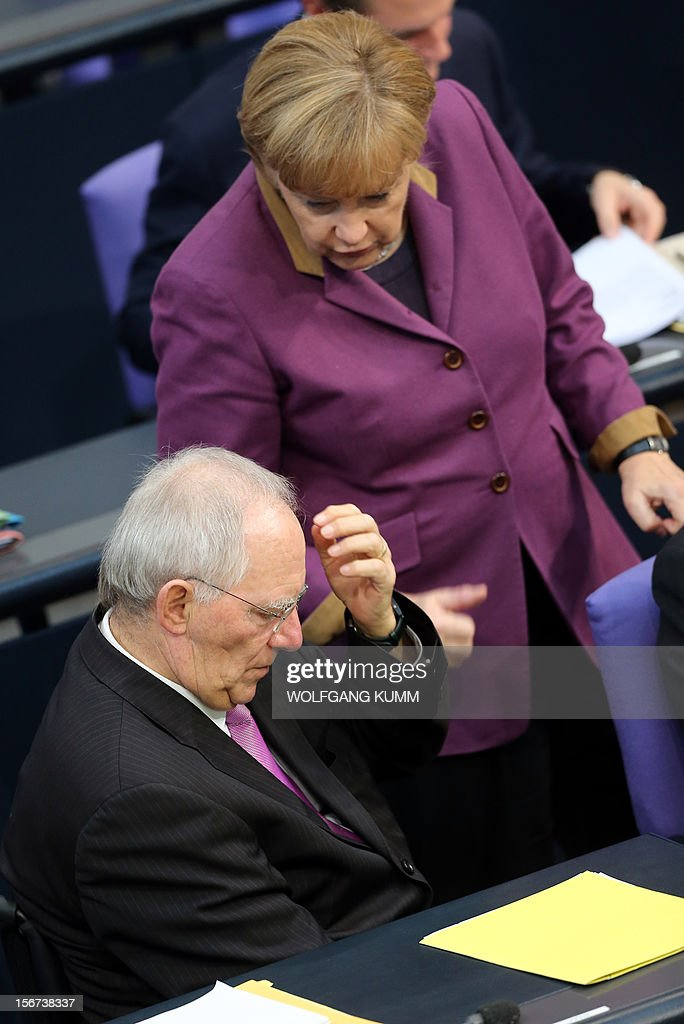 German Chancellor Angela Merkel (R) talks with German Finance minister Wolfgang Schaeuble on November 20, 2012 in Bundestag in Berlin. Gloomy German companies are preparing to slash their workforces next year as the eurozone crisis bites, a survey showed on Monday, with more than one in four firms saying they would cut jobs in 2013. AFP PHOTO/ Wolfgang Kumm/ GERMANY OUT